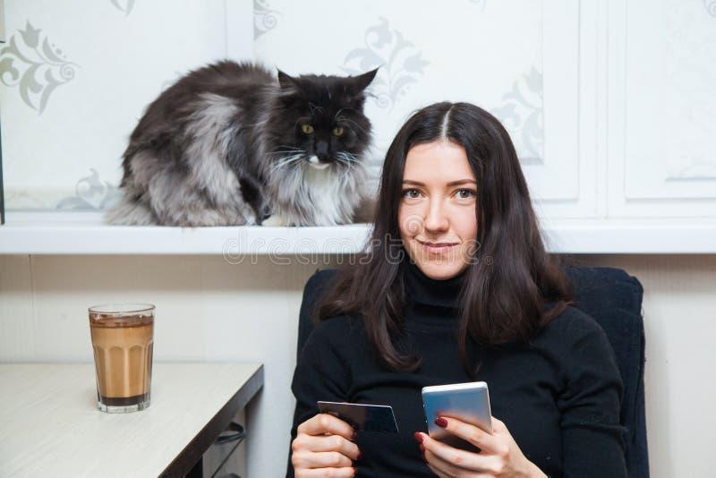 少妇和猫在网上买事与信用卡和巧妙的电话 库存照片