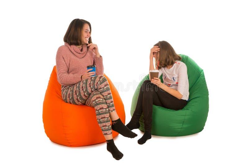 少妇和笑的女孩坐装豆子小布袋椅子和drin 免版税库存照片