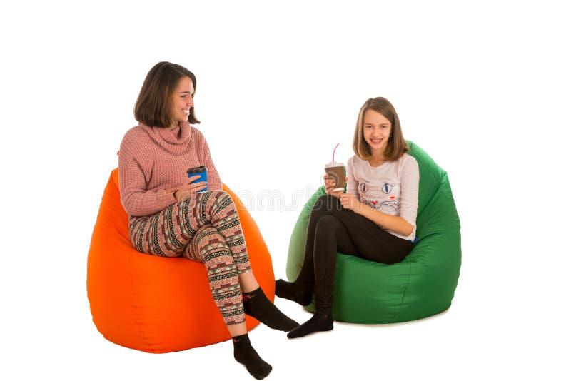 少妇和逗人喜爱的女孩坐装豆子小布袋椅子和喝 免版税库存图片