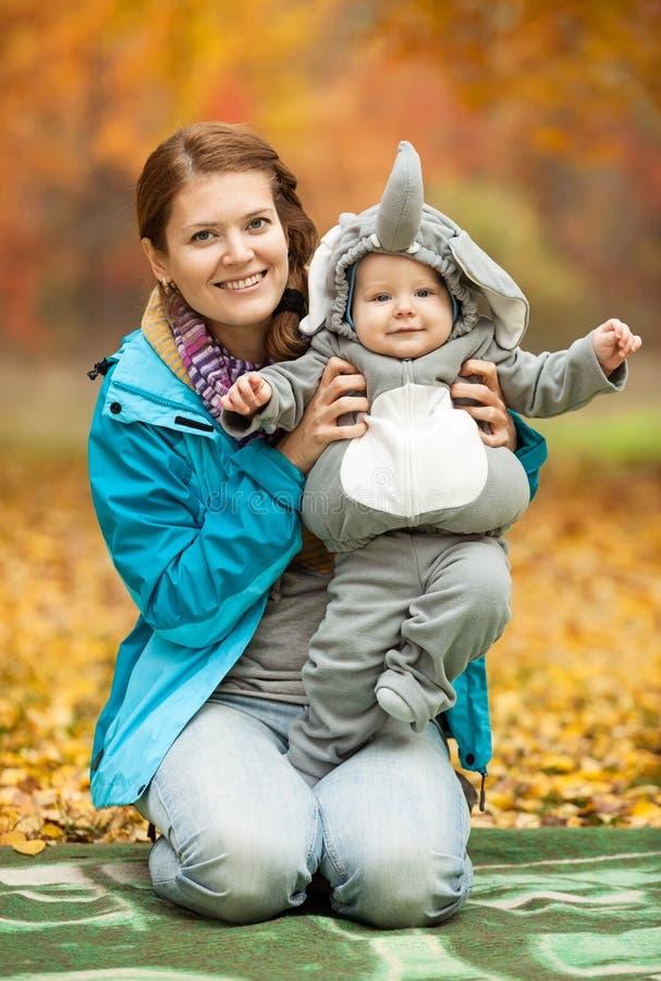 少妇和婴孩在大象服装穿戴了 库存图片