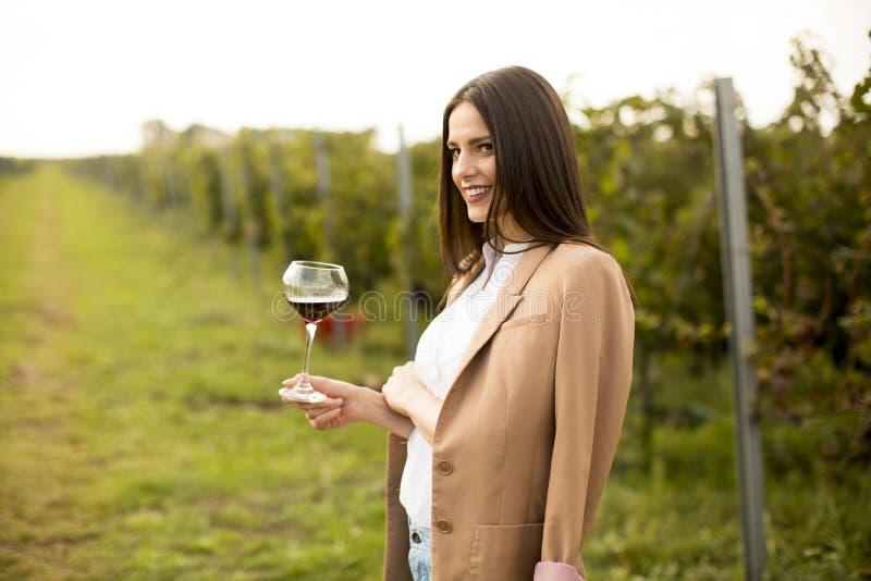 少妇品尝酒在葡萄园里 免版税库存照片