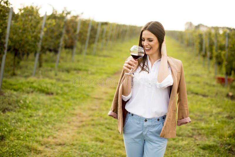少妇品尝酒在葡萄园里 免版税库存图片