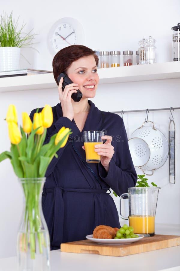 妇女喝一杯橙汁和谈话在电话 库存图片