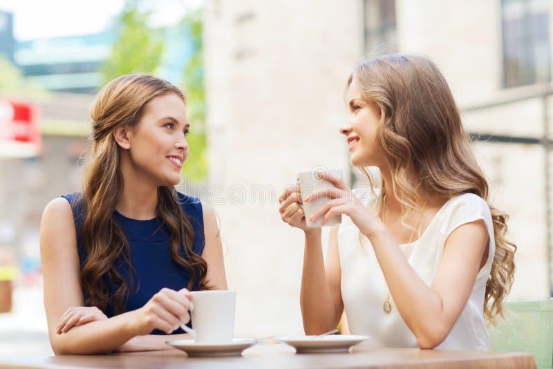 少妇喝咖啡和谈话在咖啡馆 库存照片