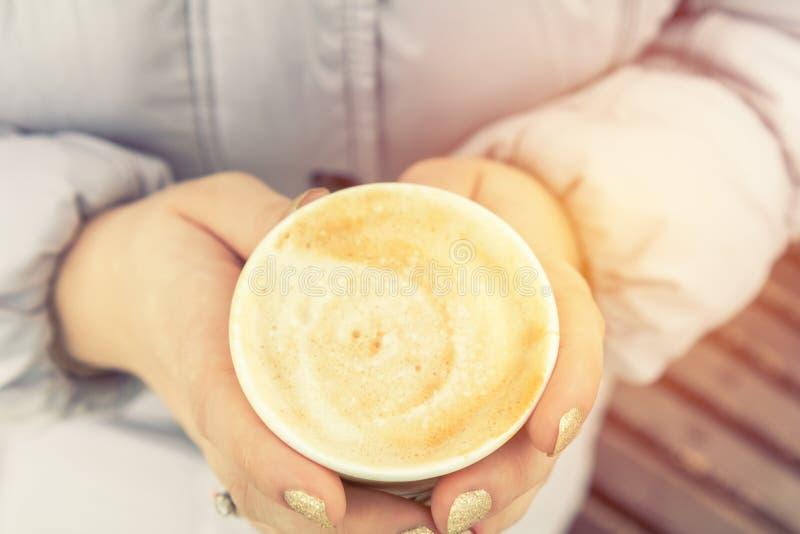 少妇喝在街道上的咖啡 免版税图库摄影