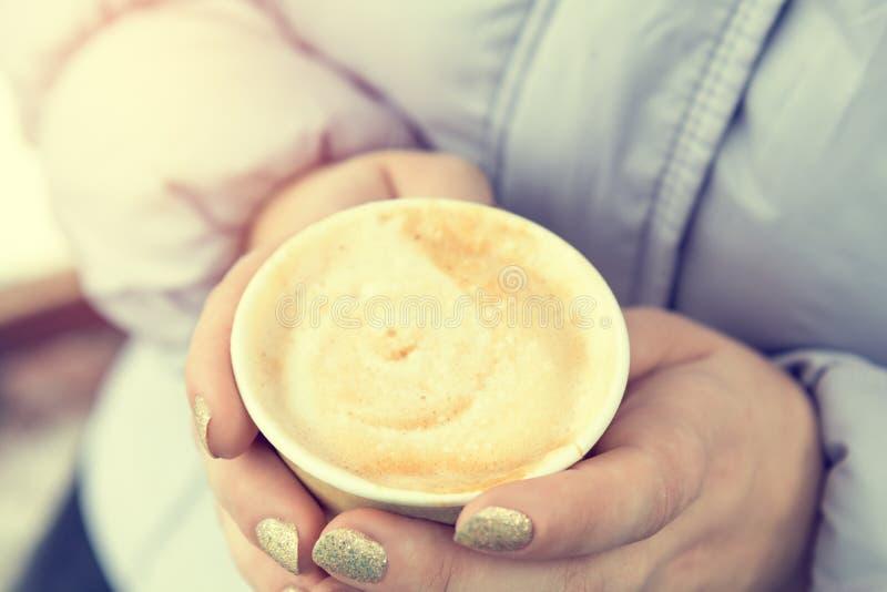 少妇喝在街道上的咖啡 免版税库存图片