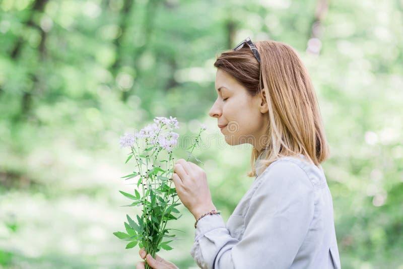 少妇嗅到的花本质上 免版税库存照片