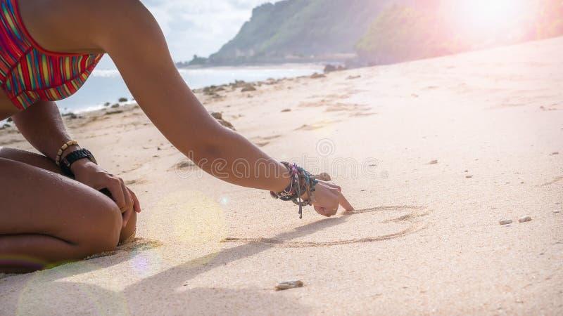 少妇图画在沙子在海滩,巴厘岛的心脏形状 免版税库存图片