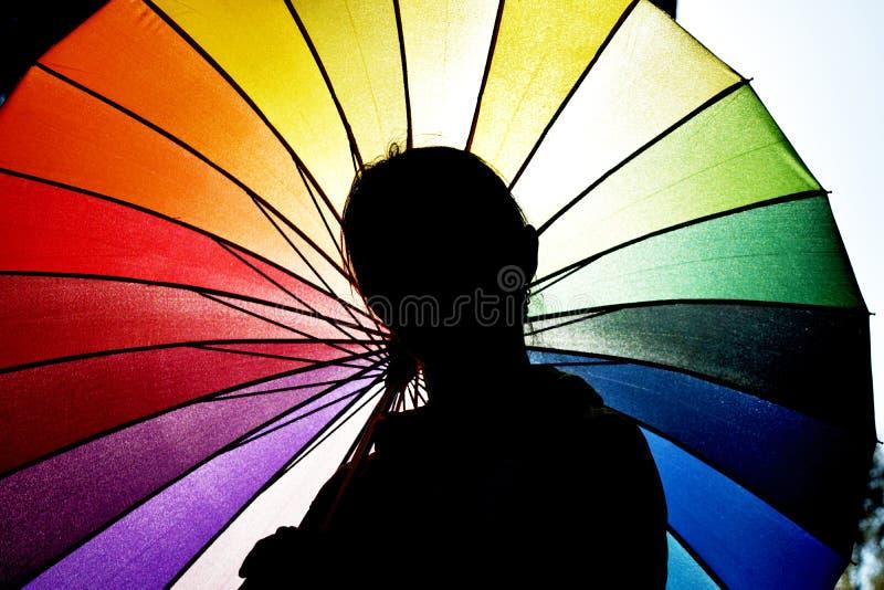 少妇在一把五颜六色的伞下 一个女孩的剪影反对彩虹伞的 走在明亮的伞下的少妇 库存照片