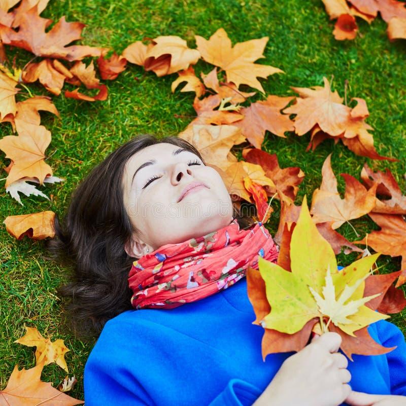 少妇在一秋天天,放置在与五颜六色的秋叶的地面上 库存图片