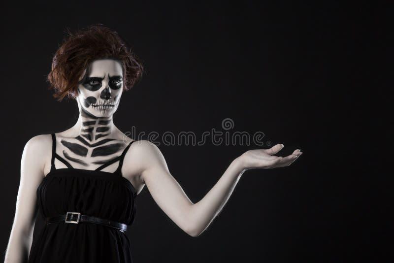 少妇在停止的屏蔽头骨表面艺术的日 万圣节与雾的表面艺术在黑色背景 库存图片