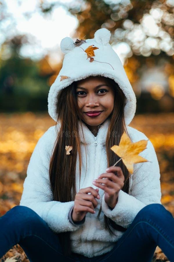 少妇在公园在晴朗的秋天天,微笑,举行离开 白色毛线衣的快乐的美丽的女孩 免版税库存照片
