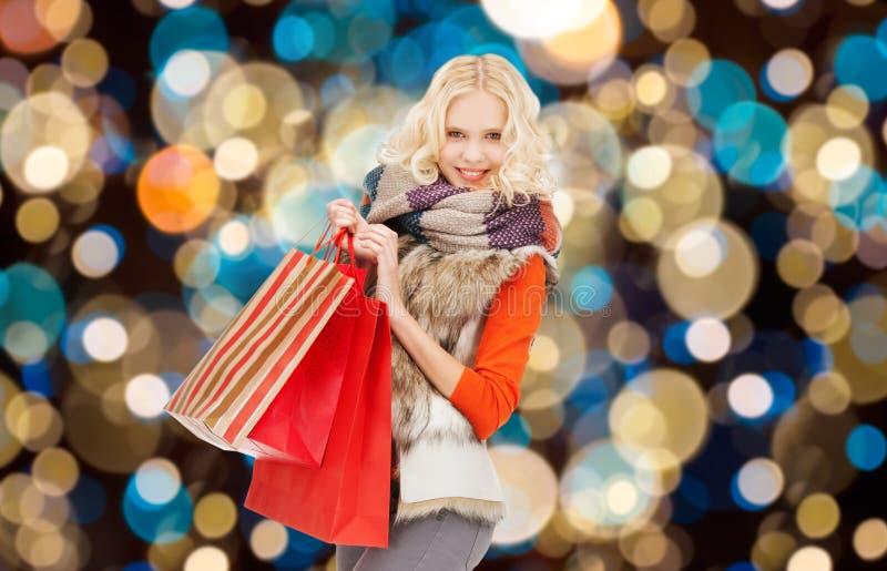 少妇在冬天穿衣与购物袋 免版税库存照片