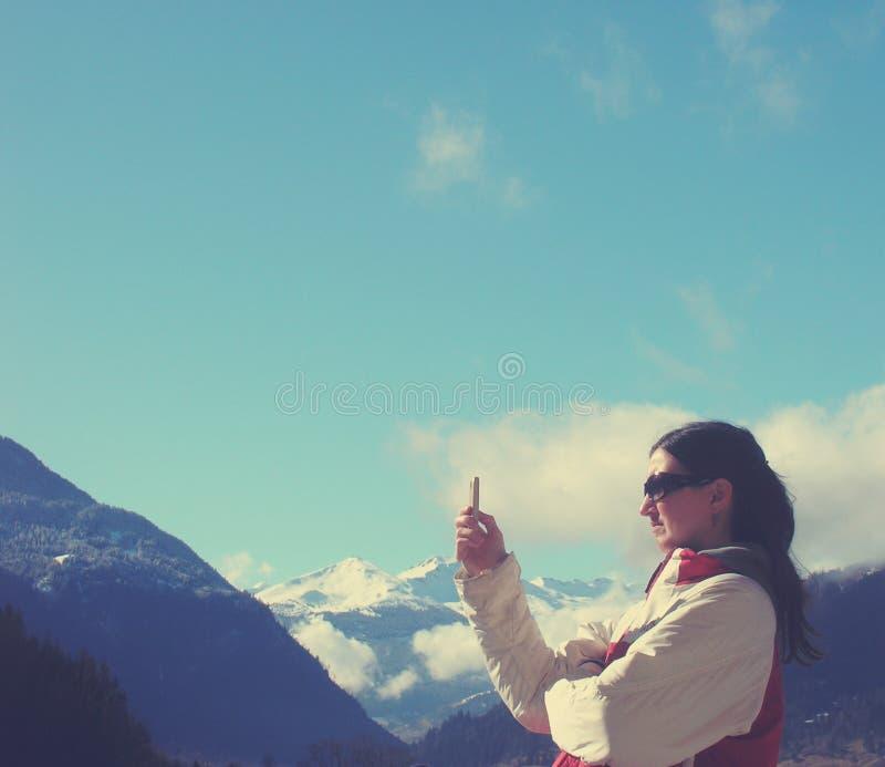 少妇在冬天给发短信在手机穿衣;减速火箭的样式 免版税库存图片