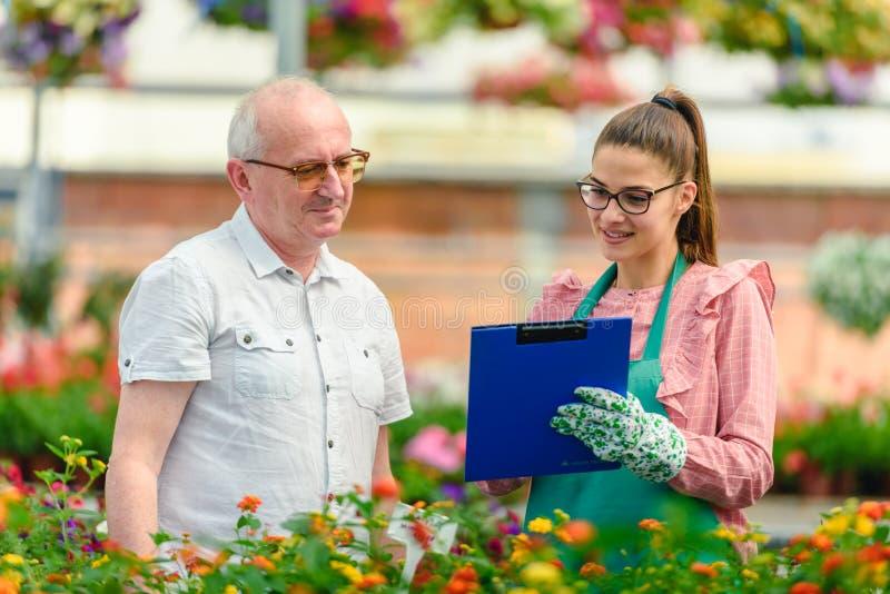 少妇在园艺中心谈话与更老的男性顾客 免版税库存图片
