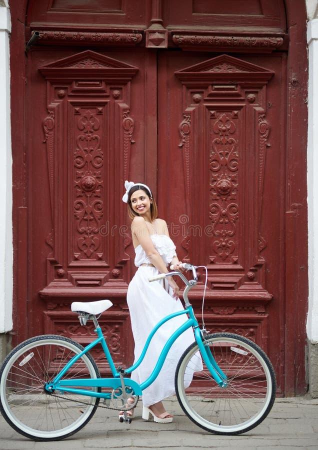 少妇在城市街道上的骑马自行车 图库摄影