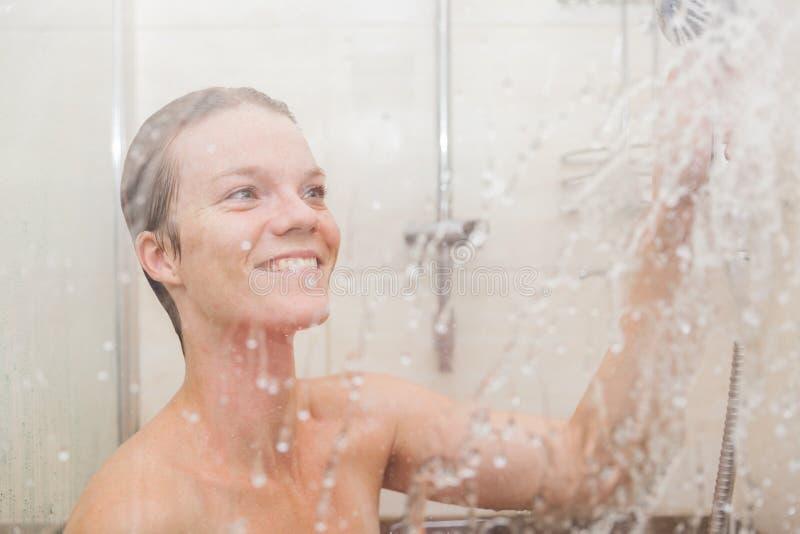 少妇在她的房子卫生间使用一场阵雨 免版税图库摄影