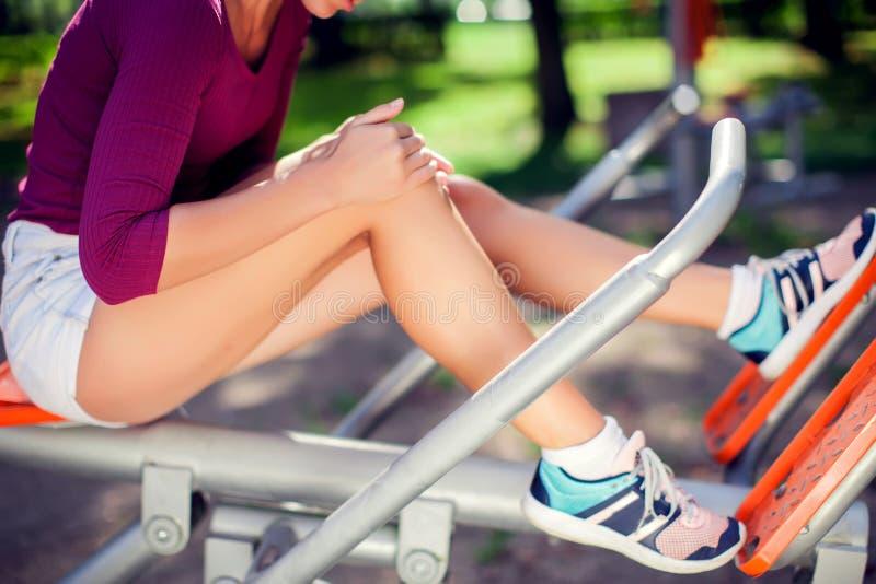 少妇在她的膝盖的感觉痛苦在的体育锻炼期间 免版税库存照片