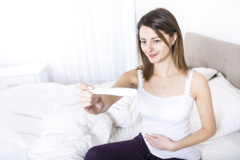 少妇在家佩带在白色检查怀孕的测试的卧室 库存照片
