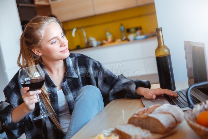 少妇在家厨房饮用的酒观看的电影的 免版税库存照片