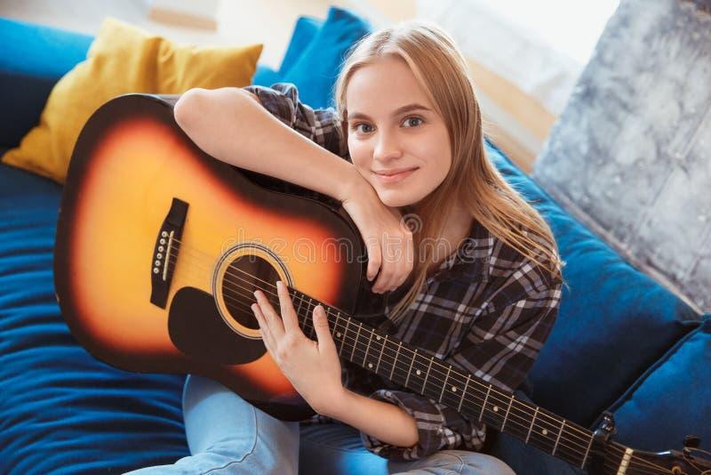 少妇在家拿着吉他的客厅爱好的 库存图片