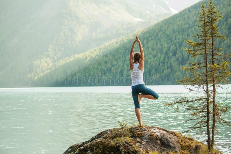 少妇在山湖实践瑜伽 免版税库存图片
