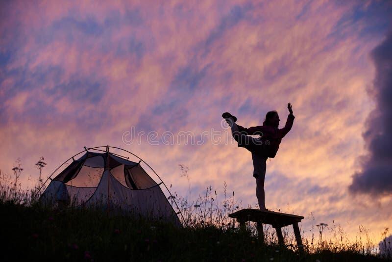 少妇在帐篷附近实践在远足的瑜伽 免版税库存照片