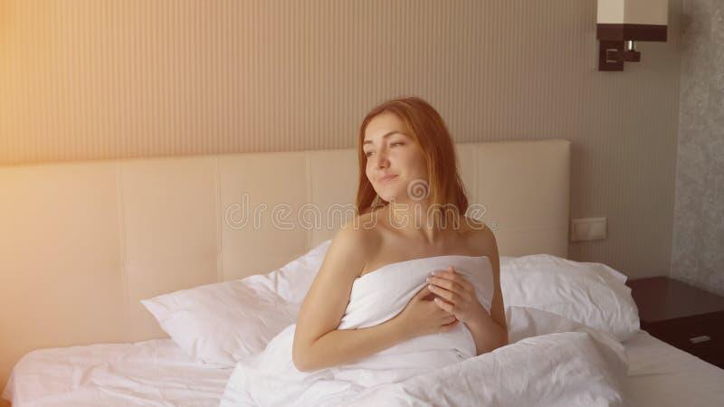 少妇在床上醒 免版税图库摄影