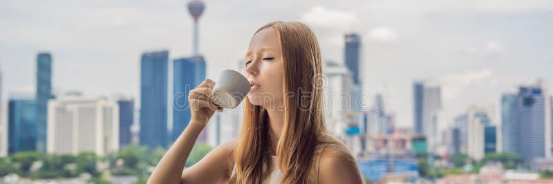 少妇在忽略大城市和摩天大楼横幅长的格式的阳台的早晨喝咖啡 免版税库存照片