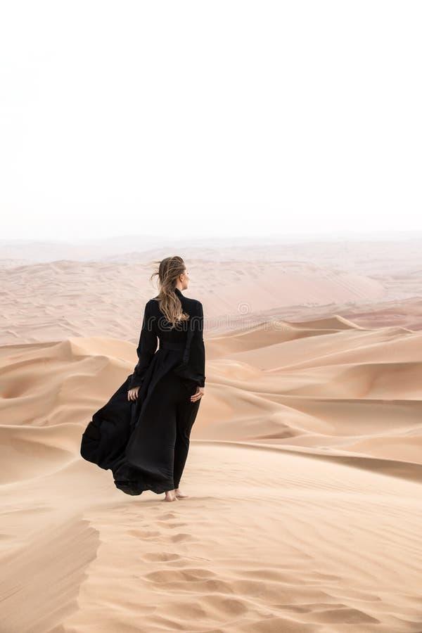 少妇在摆在沙漠风景的Abaya 免版税图库摄影
