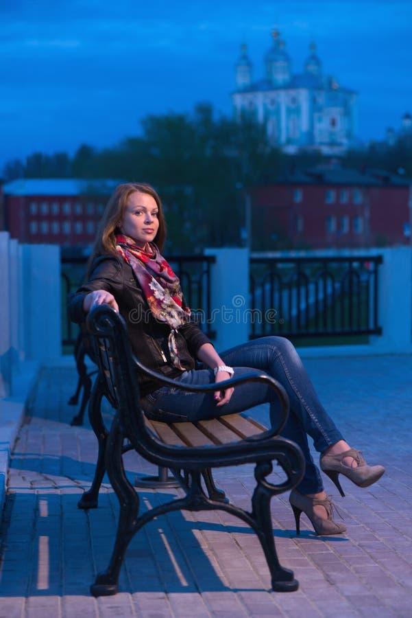 少妇在晚上在城市公园 免版税图库摄影