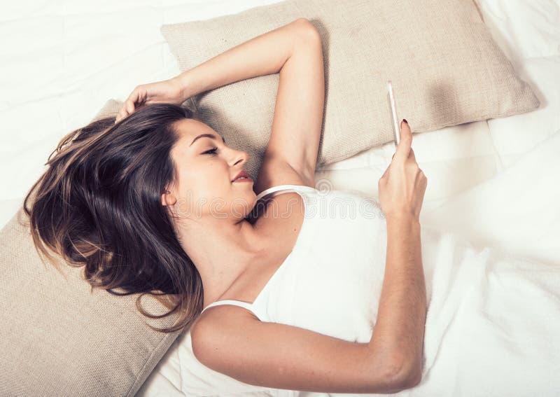少妇在有手机的卧室在卧室 免版税库存照片