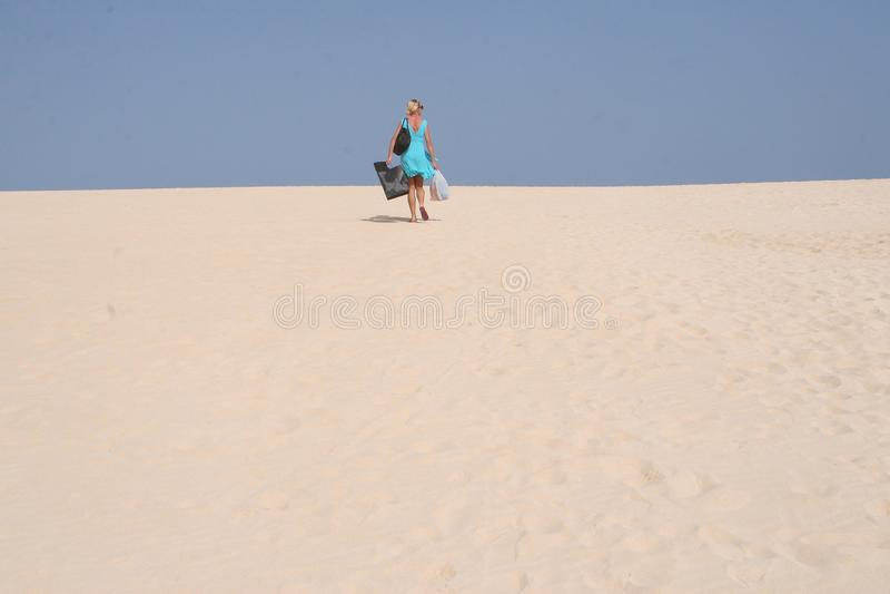 少妇在有沙子沙丘的国家公园在Corralejo附近海滩在费埃特文图拉岛在西班牙 库存照片