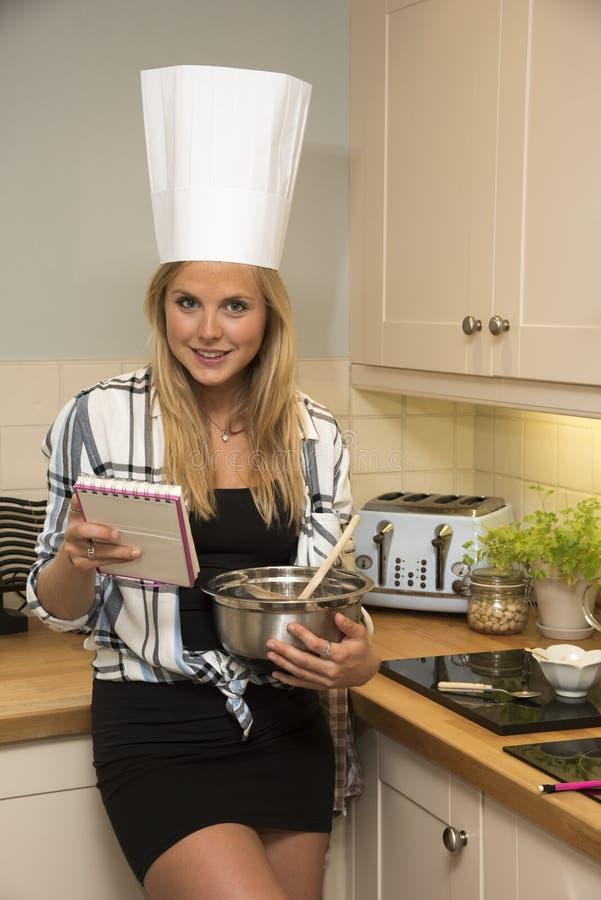 少妇在有混料盆的厨房里 免版税库存图片