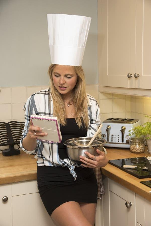 少妇在有混料盆的厨房里 免版税库存照片