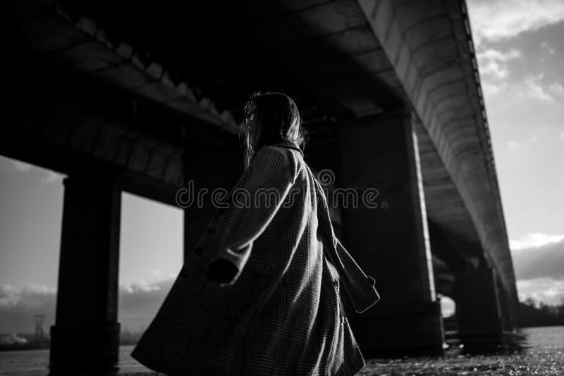 少妇在河岸走在桥梁下 黑白图象 免版税图库摄影