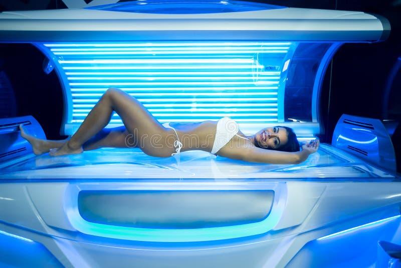 少妇在现代日光浴室 免版税库存照片