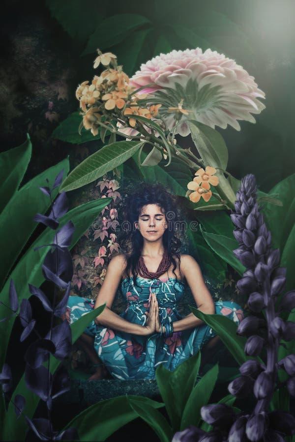 少妇在瑜伽位置思考在幻想庭院 免版税库存图片