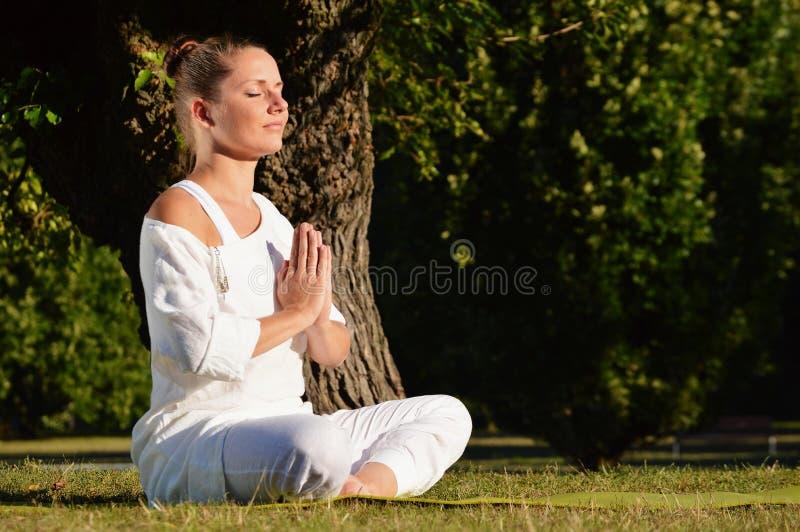 少妇在瑜伽凝思时在公园 库存照片