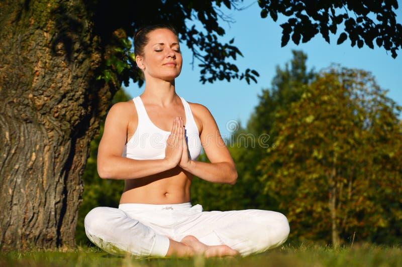 少妇在瑜伽凝思时在公园 免版税库存图片