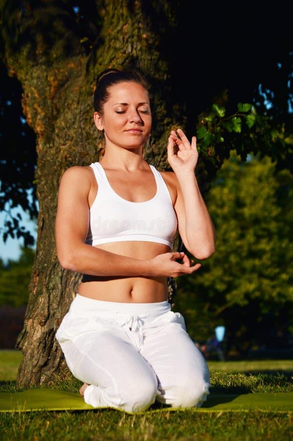 少妇在瑜伽凝思时在公园 免版税库存照片