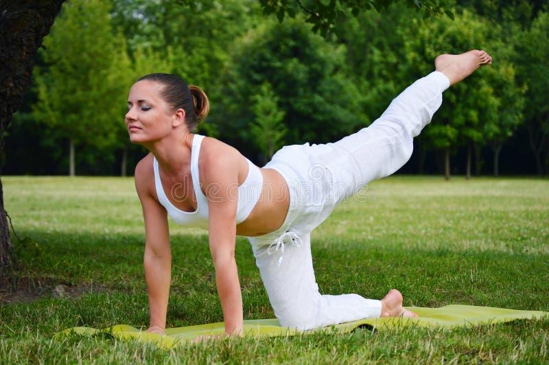 少妇在瑜伽凝思时在公园 免版税图库摄影