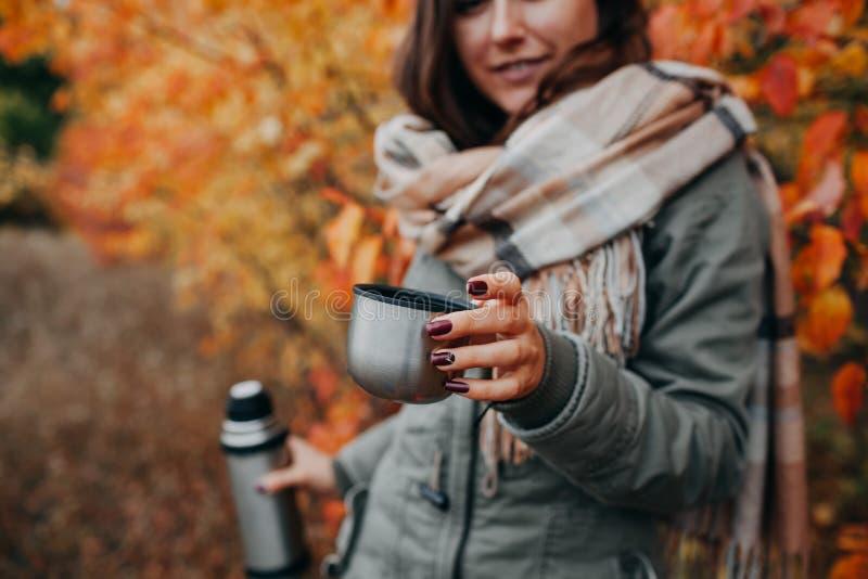 少妇在秋天森林里喝茶 库存照片
