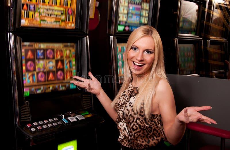 少妇在老虎机的赌博娱乐场 免版税库存照片