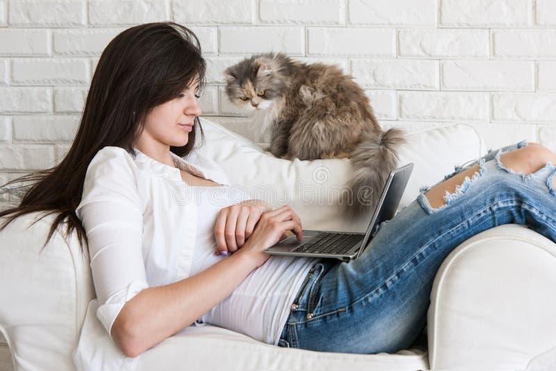 少妇在膝上型计算机和她的猫附近工作 库存照片