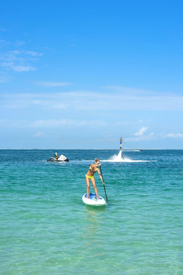 少妇在船上站起来并且供以人员摆在新的flyboard在加勒比热带海滩 直立paddleboarding 正面人e 图库摄影