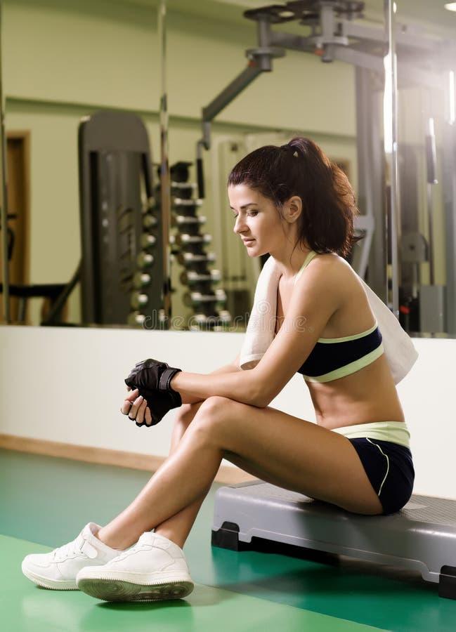 少妇在训练疲倦了在健身俱乐部以后 库存图片