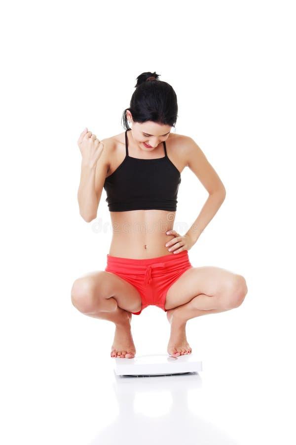 少妇在运动服蹲下。 图库摄影