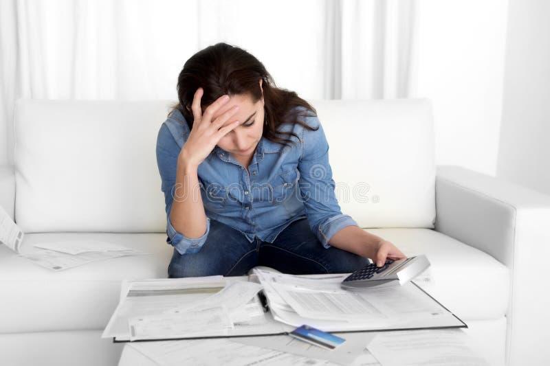 少妇在重音会计与计算器的银行票据在家担心 库存照片