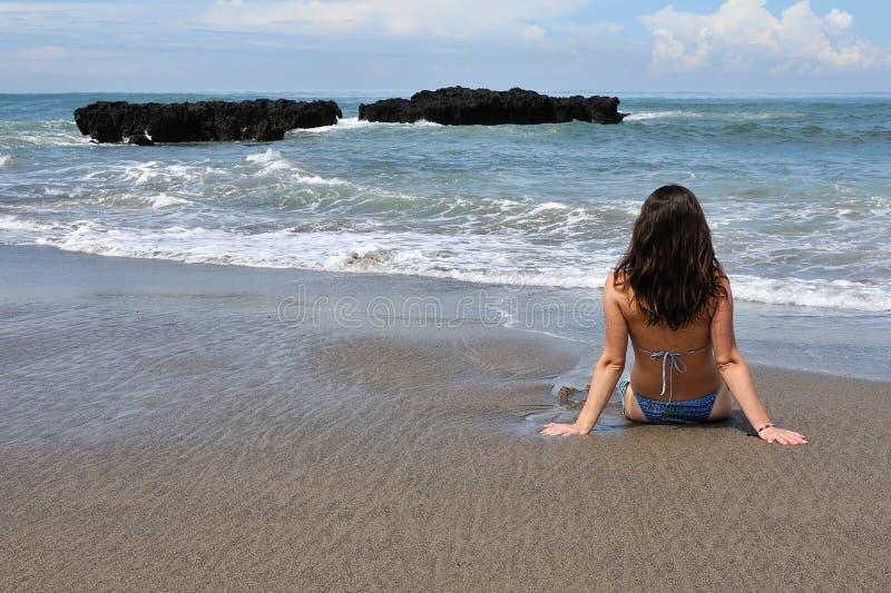 少妇在面对海洋的海边在ealy早晨 免版税库存照片